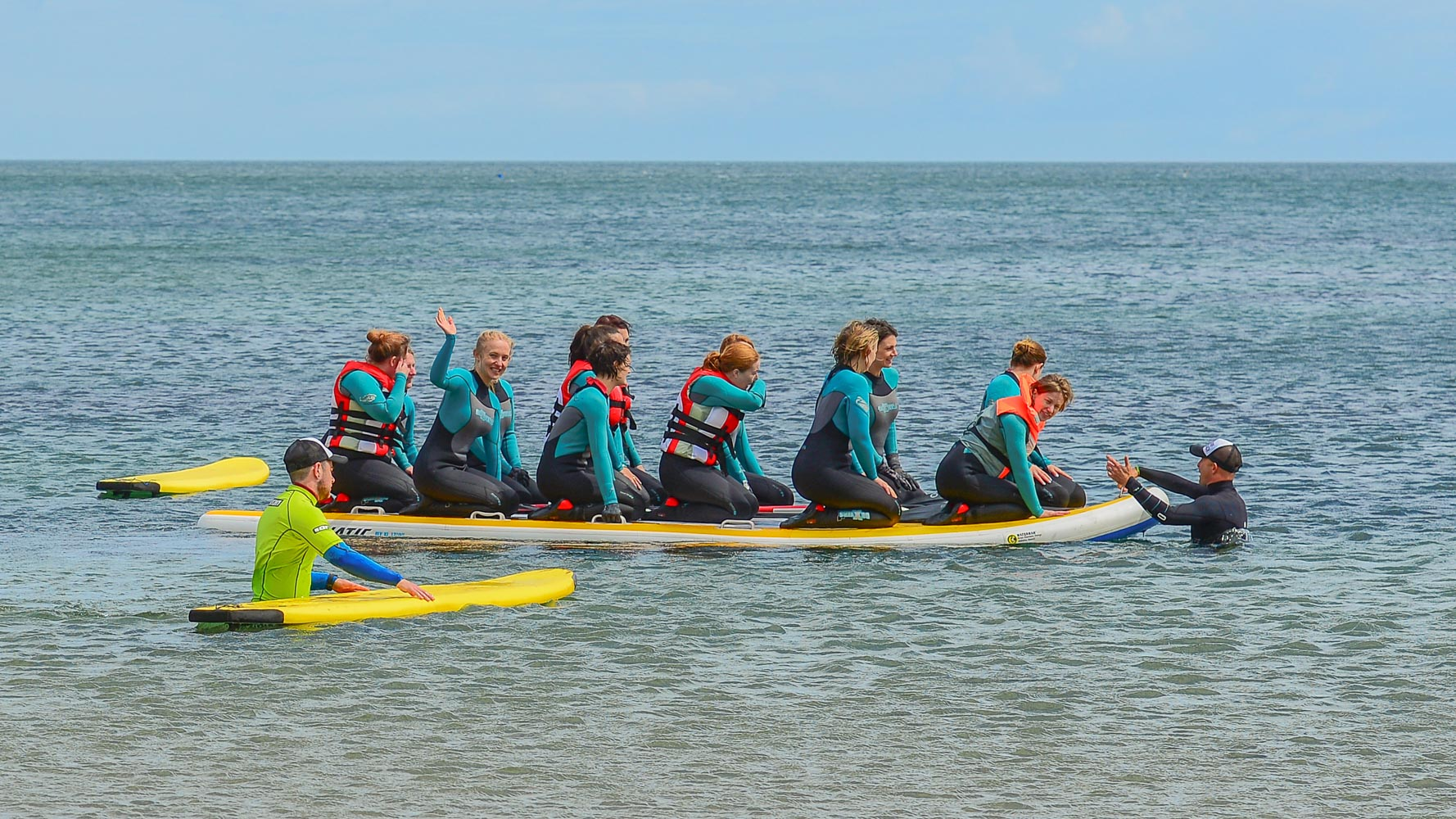 Hen Surf Party all paddling on a 10 person surfboard