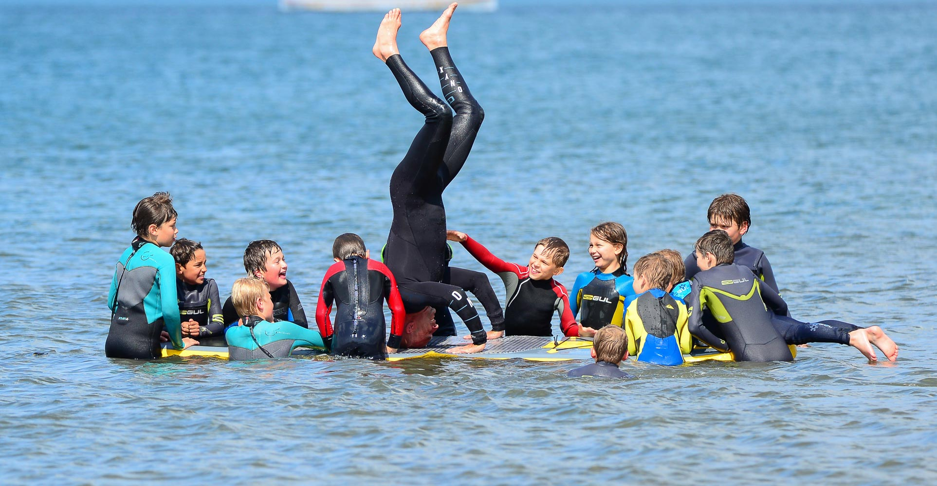 Kids Surf Club, Instructor doing a handstand on a surfboard