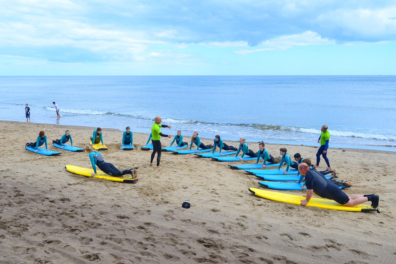 The start of a group surf lesson, learning on the beach!